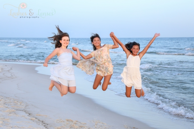 Girl cousins jumping by the edge of the water at Johnson Beach Perdido Key