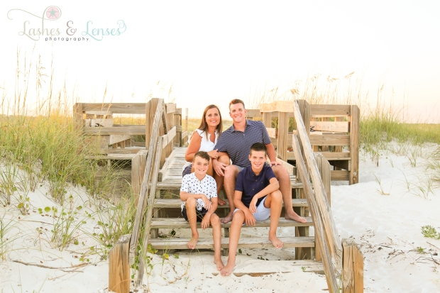 Mom and Dad with sons sitting on steps going down to the beach at Johnsons Beach in Perdido Key