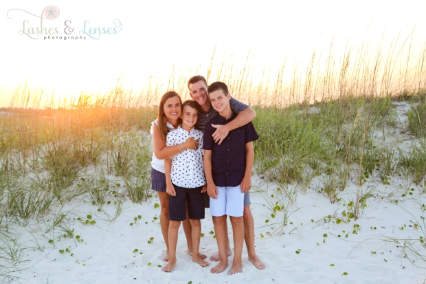 Parents hugging their boys next to a sand dune at Johnsons Beach in Perdido Key