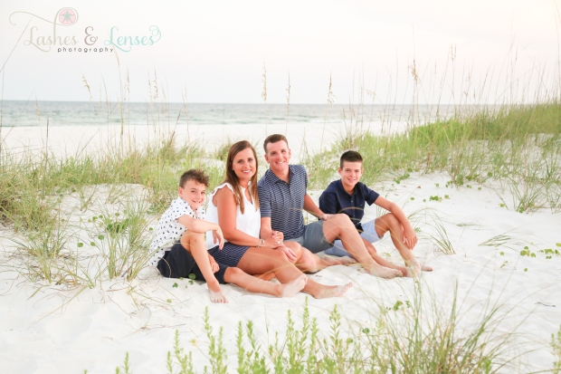 Parents sitting in the sand with their two sons at Johnsons Beach in Perdido Key