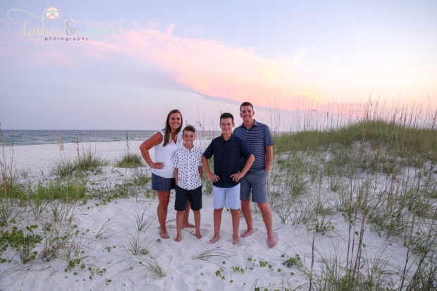 Family standing with the sunset behind them at Johnsons Beach in Perdido Key