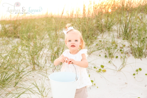 Little girl with bucket playing in the sand at Johnsons Beach in Perdido Key