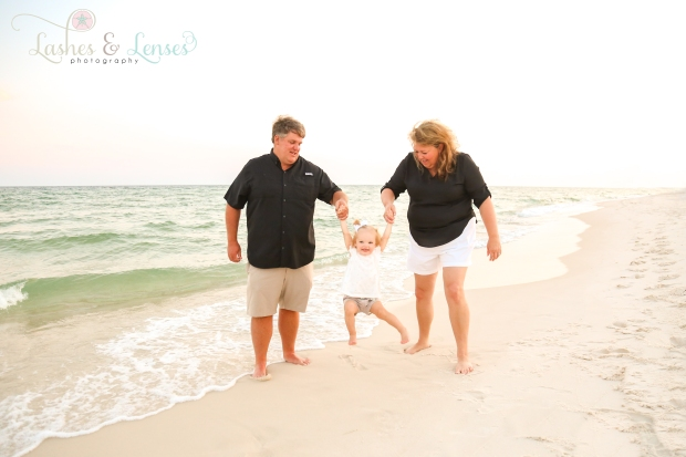 Grandparents with granddaughter walking by the water at Johnsons Beach in Perdido Key