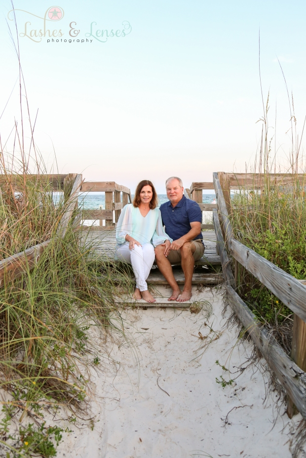 Middle-aged couple sitting on the steps on the boardwalk at Johnsons Beach in Perdido Key