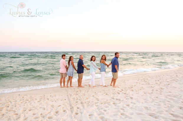 Family with adult children looking towards the camera by the water at Johnsons Beach in Perdido Key