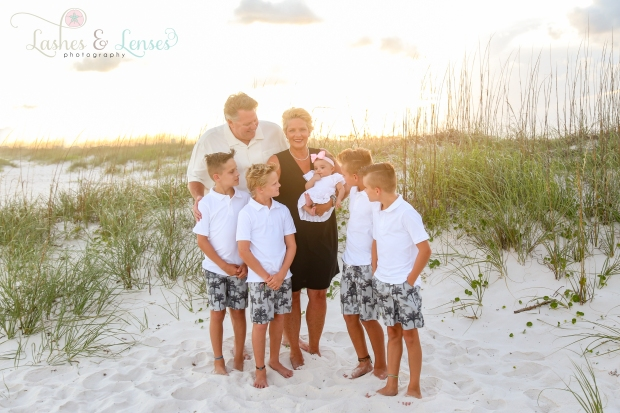 Grandparents with grandchildren surrounding them by a sand dune at Johnsons Beach Perdido Key