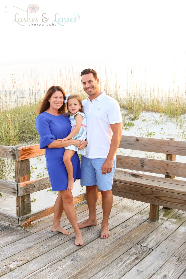 Parents with toddler daughter standing on the boardwalk at Johnsons Beach in Perdido Key