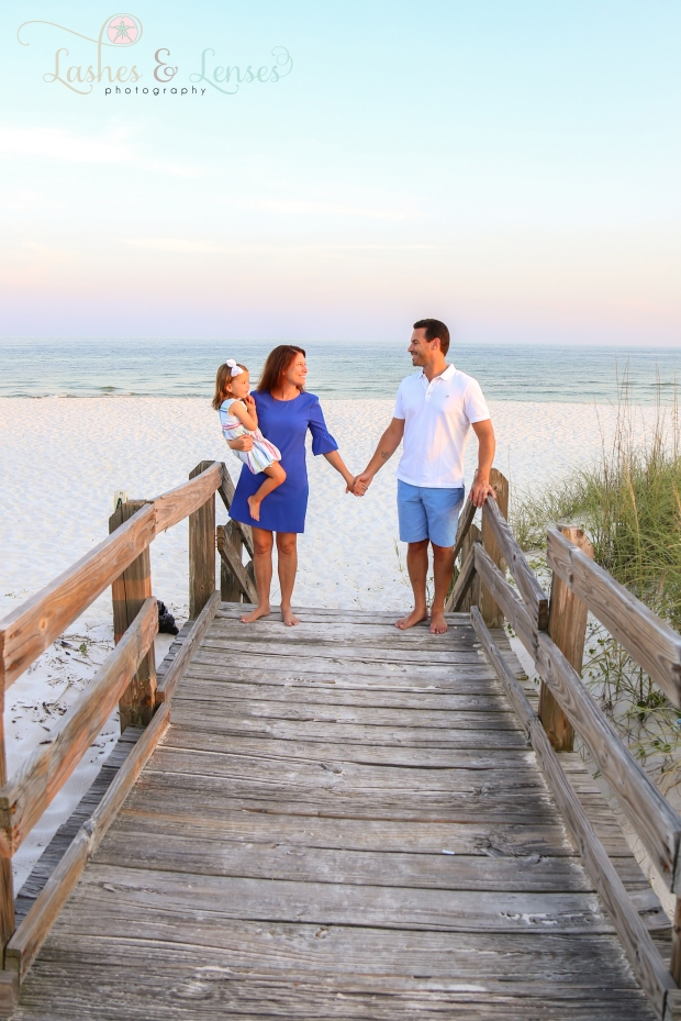 Parents with toddler daughter holding hands and looking at each other  on the boardwalk at Johnsons Beach in Perdido Key