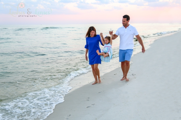 Mom and Dad swinging daughter off her feet by the waters edge at Johnsons Beach in Perdido Key