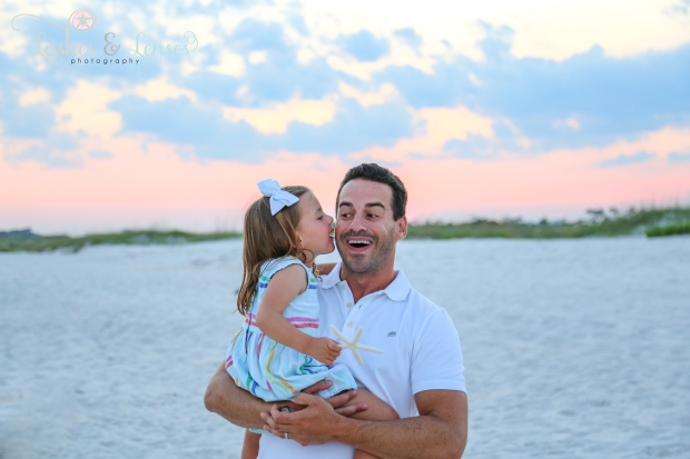 Daughter telling her daddy a secret at Johnsons Beach in Perdido Key
