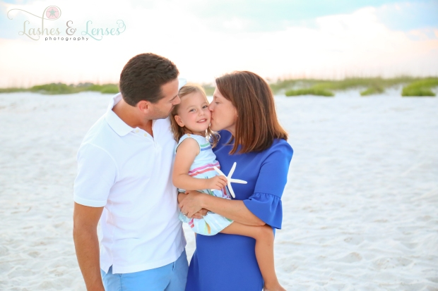 Parents kissing daughter on the cheek at Johnsons Beach in Perdido Key