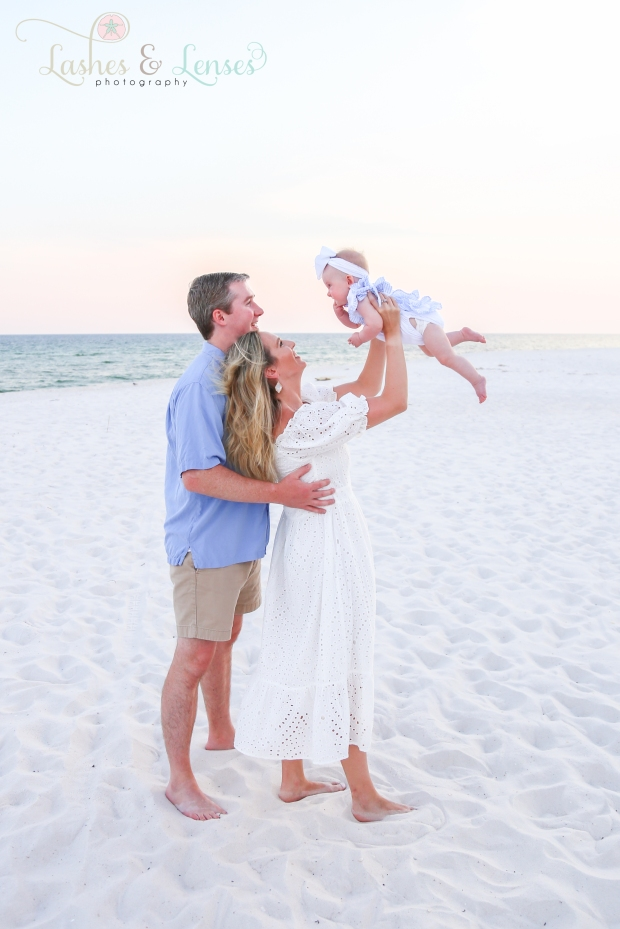 Mom holding baby girl with Dad standing behind mom on the beach at Johnsons Beach in Perdido Key