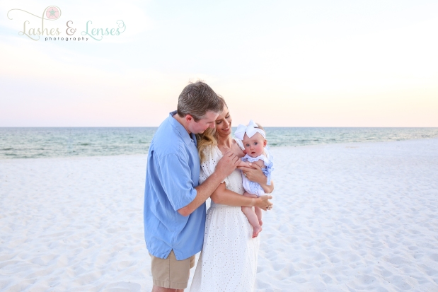 Parents holding baby girl on the beach on the beach at Johnsons Beach in Perdido Key