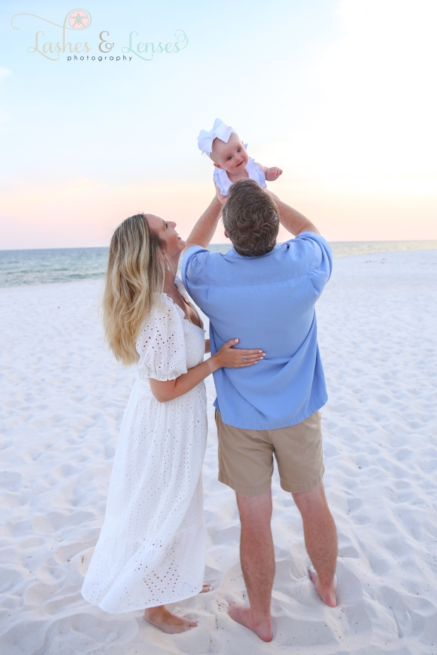 Dad holding baby girl on the beach on the beach at Johnsons Beach in Perdido Key