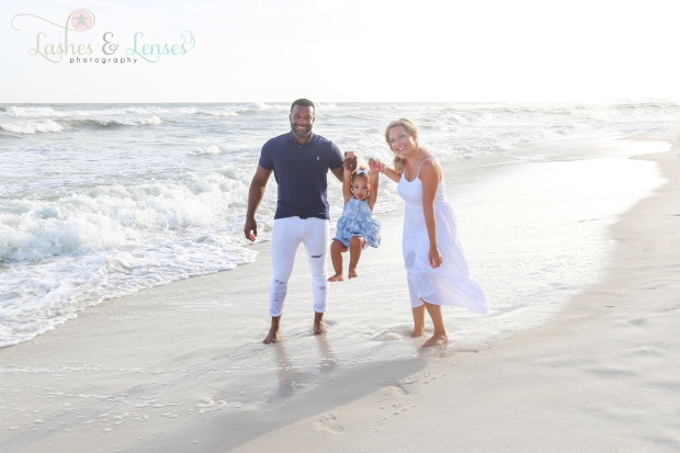 Mom and Dad swinging little girl down by the water in Perdido Key