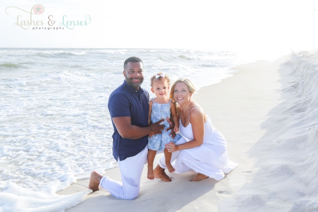 Parents kneeling down with daughter in between them by the water in Perdido Key