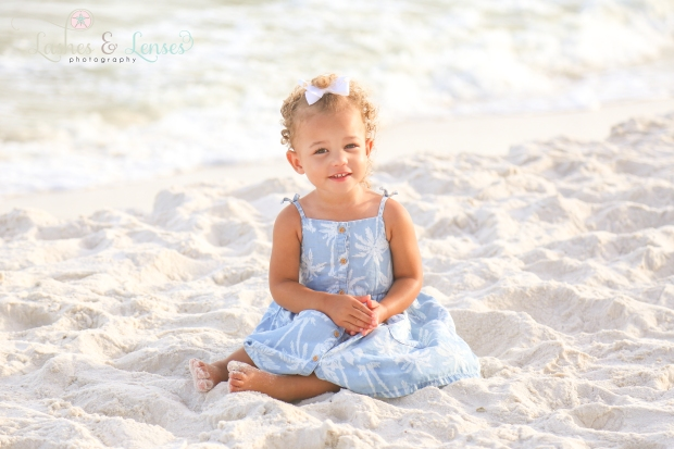 Sweet toddler girl sitting in the sand on the beach in Perdido Key