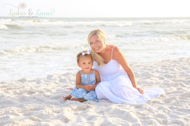 Mom sitting in the sand with her toddler daughter by the water in Perdido Key