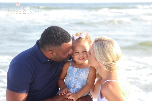 Mom and Dad kissing daughter on the cheek by the water in Perdido Key