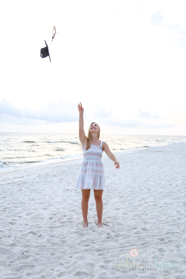 Senior Girl portrait throwing graduation cap in the air at Johnson's Beach in Perdido Key
