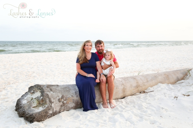 Mom, dad, and daughter sitting on a washed up log on the beach at Johnsons Beach in Perdido Key