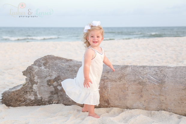 Toddler girl standing by washed up log on the beach at Johnsons Beach in Perdido Key