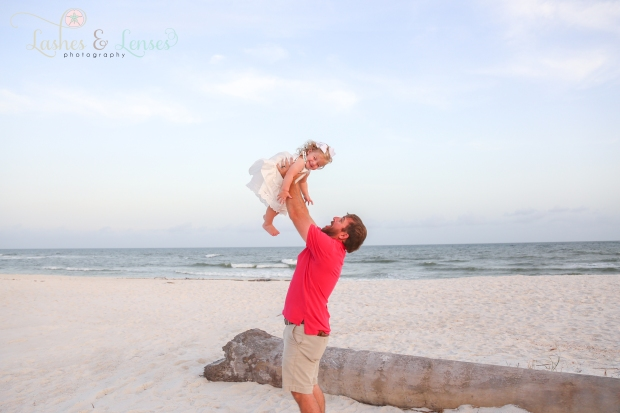 Dad throwing little girl in the air beach at Johnsons Beach in Perdido Key