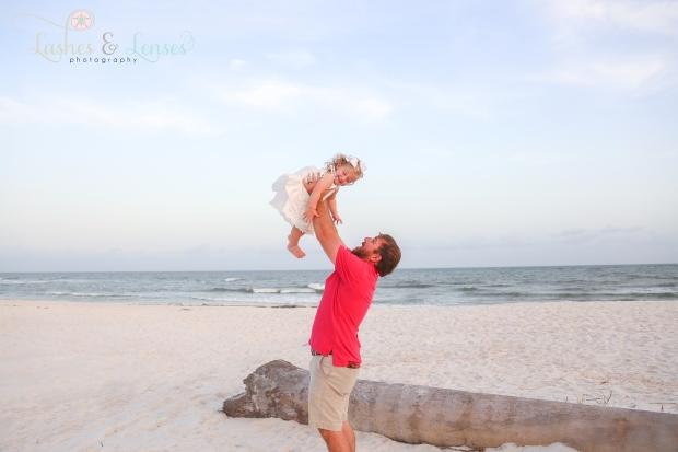 Dad throwing little girl in the air beach at Johnsons Beach in Perdido Key