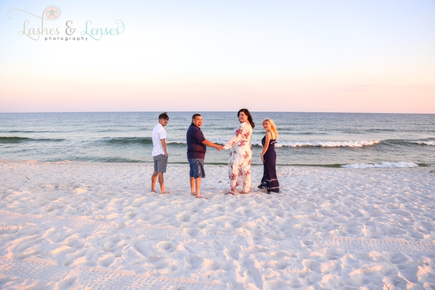 Parents with teenage children looking over their shoulders by the waters edge at Johnsons Beach in Perdido Key