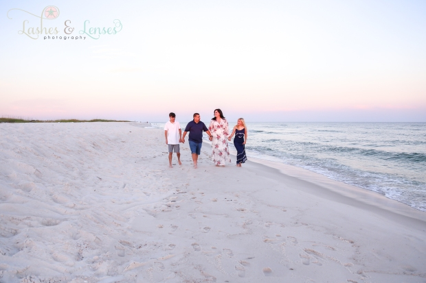 Family walking on the beach by the edge of the water at Johnsons Beach in Perdido Key