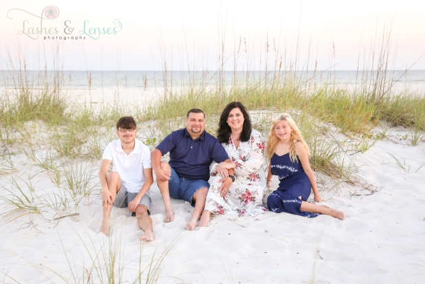 Family with teenage son and daughter sitting in the sand at Johnsons Beach in Perdido Key