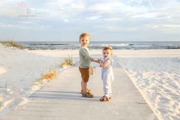 Toddler Brother and Baby Sister standing on boardwalk at Johnsons Beach in Perdido Key