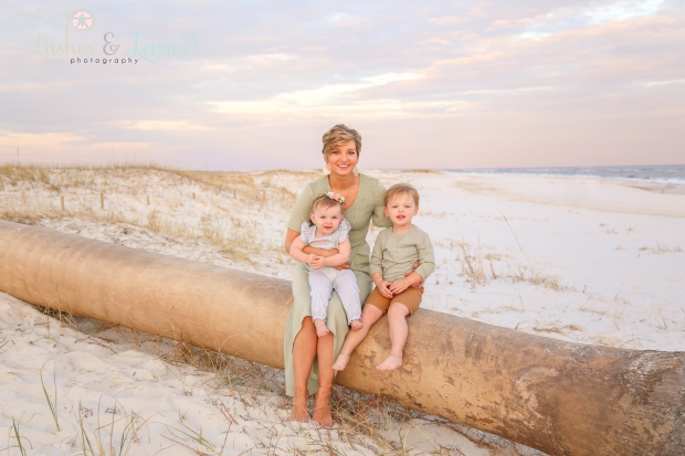 Mom with son and daughter sitting on palm tree on the beach at Johnsons Beach in Perdido Key