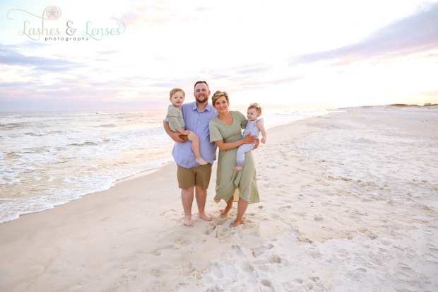Mom and Dad with children standing on the beach at Johnsons Beach in Perdido Key