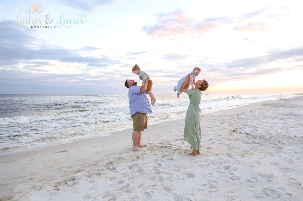 Mom and Dad throwing son and daughter in the air at Johnsons Beach in Perdido Key
