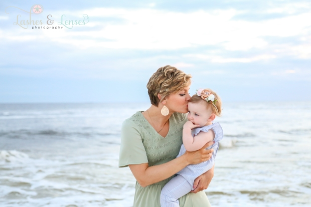 Mom kissing daughter on the head at Johnsons Beach in Perdido Key