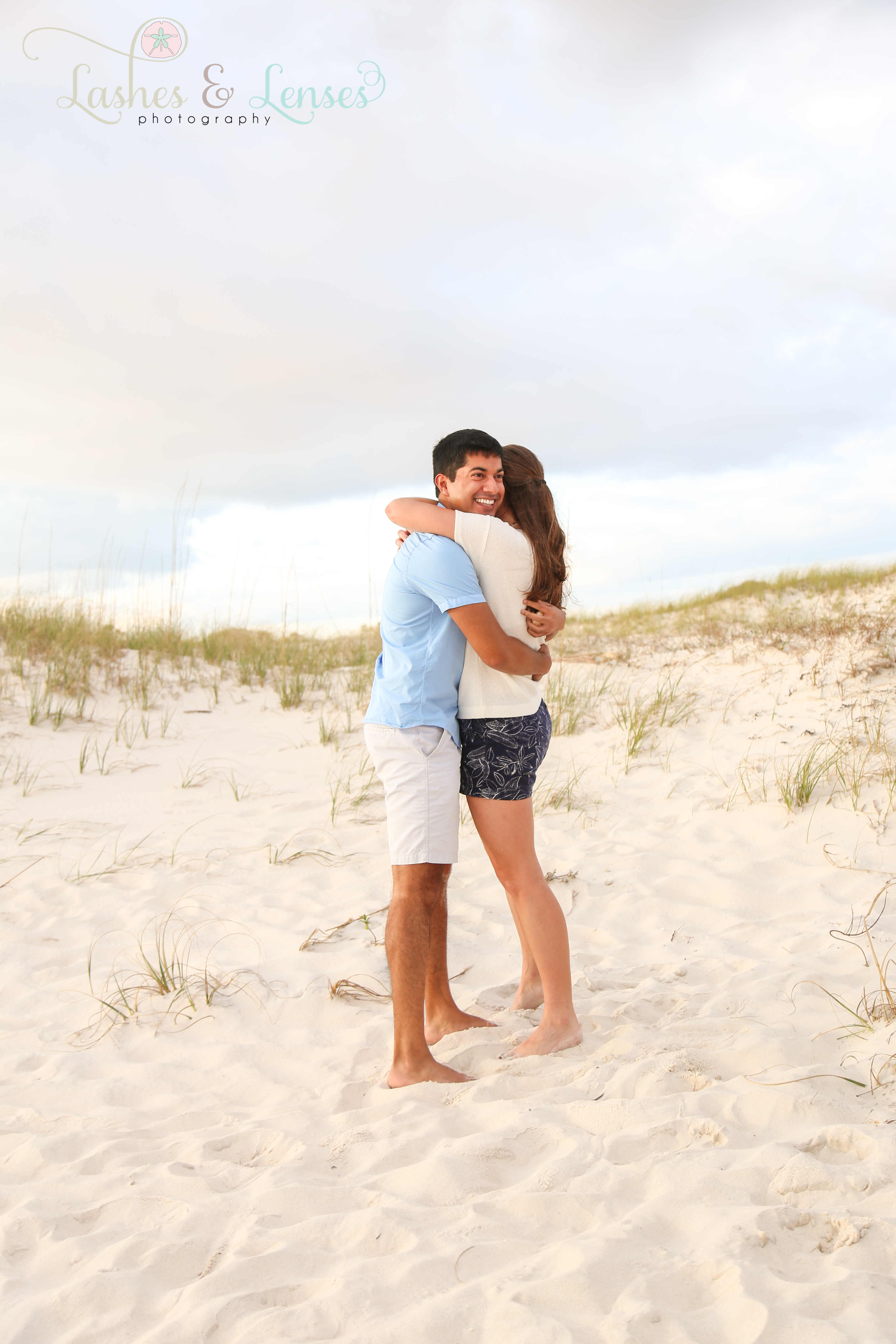 Couple hugging after getting engaged on the beach at Johnson's Beach in Perdido Key