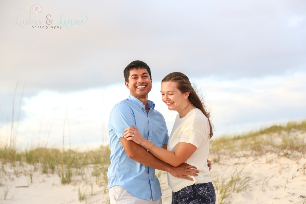 Newly engaged young woman looking at her ring on the beach at Johnson's Beach in Perdido Key