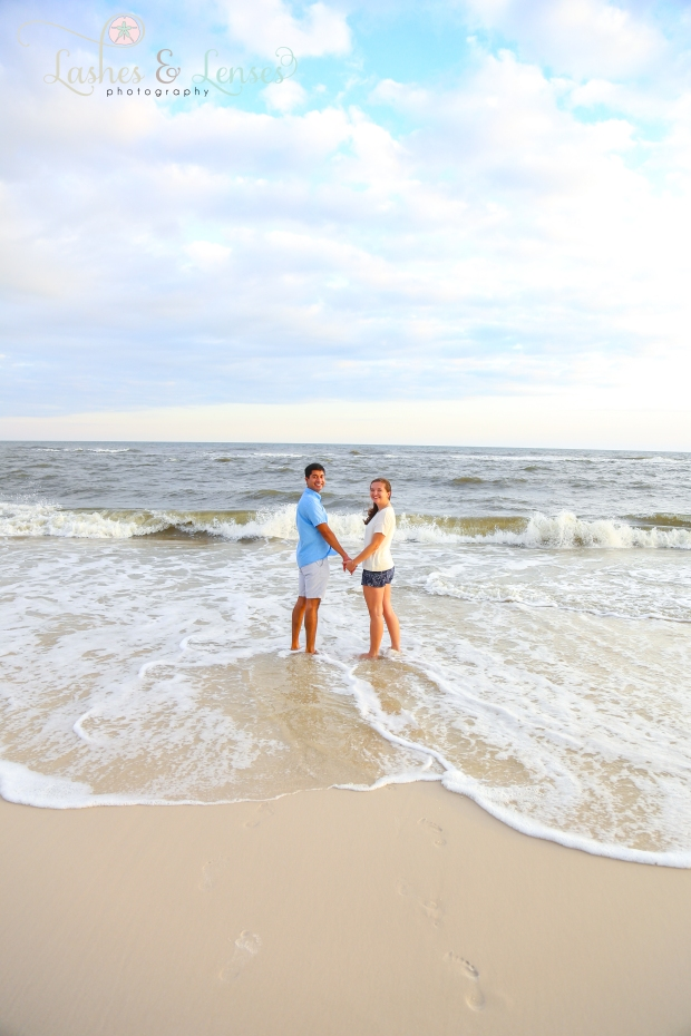 Newly Engaged couple in the water looking back at the camera at Johnson's Beach in Perdido Key