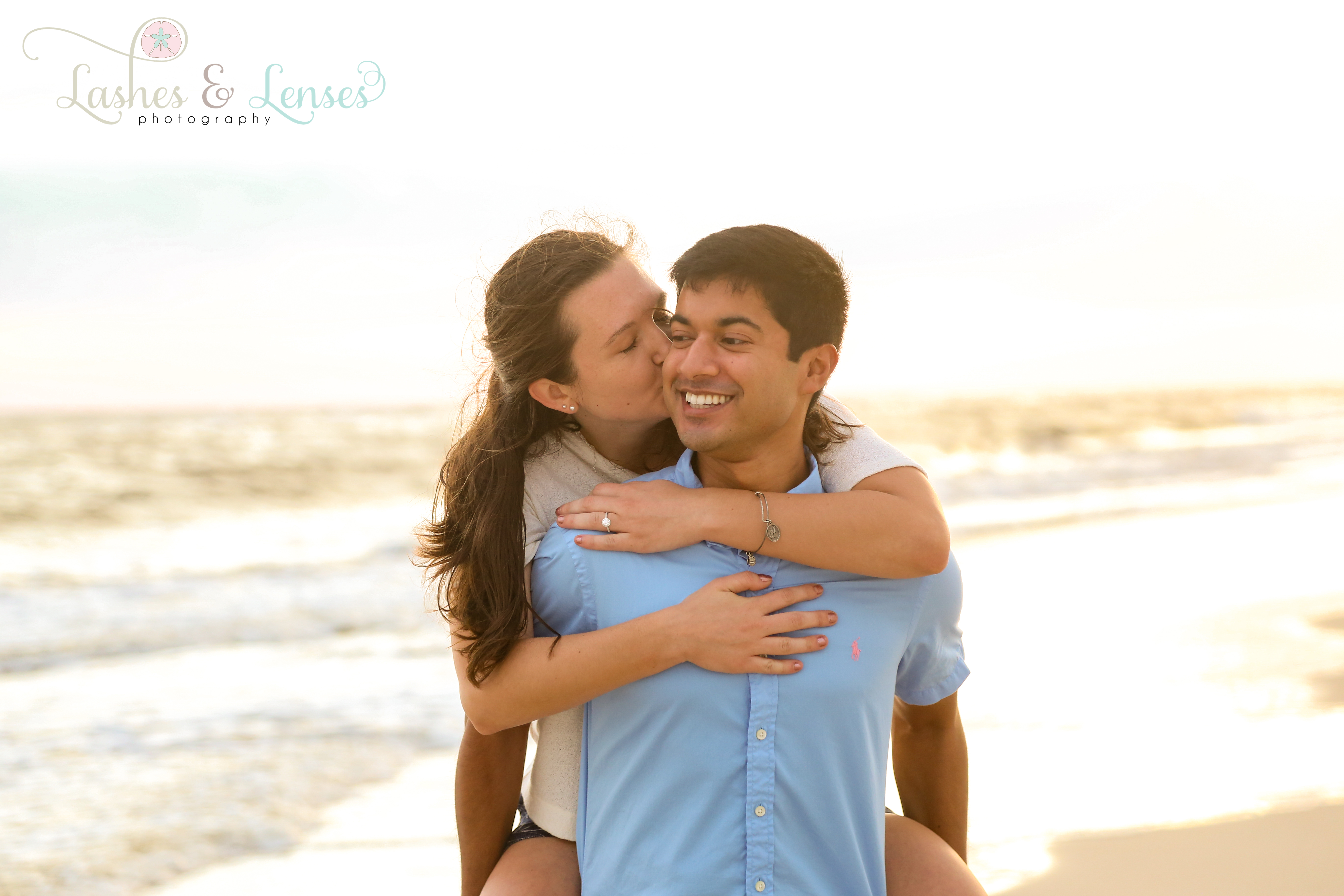 Fiancee kissing her new fiancé's cheek on the beach at Johnson's Beach in Perdido Key