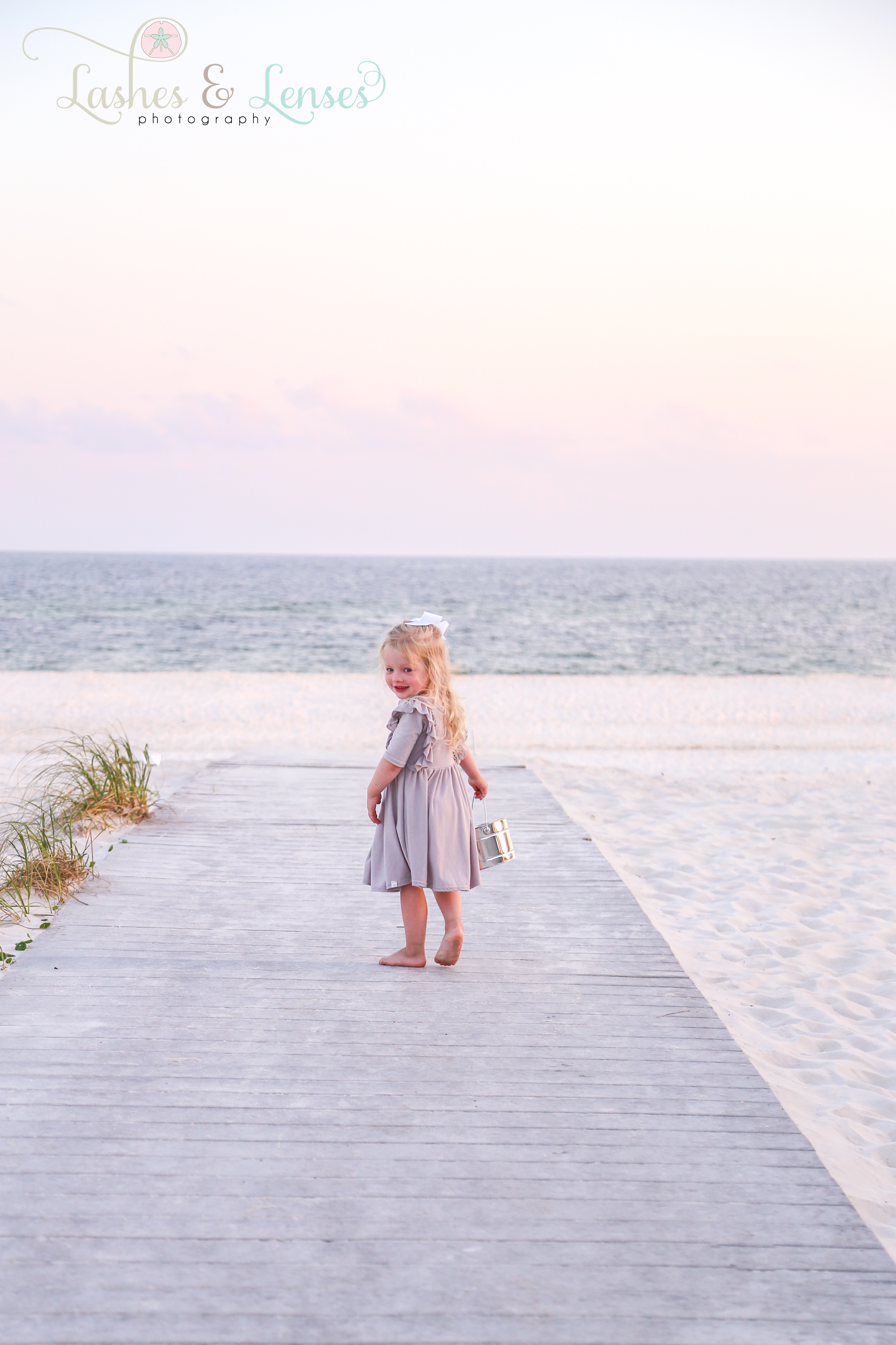 Little girl with bucket facing the camera at Johnson's Beach in Perdido Key
