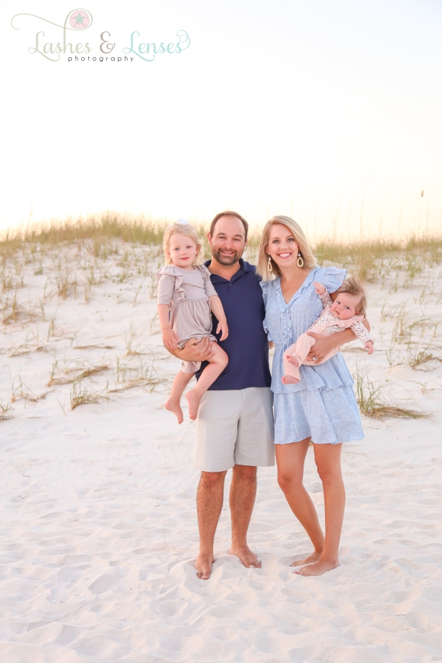 Mom and Dad with two young daughters by the sand dunes at Johnson's Beach in Perdido Key