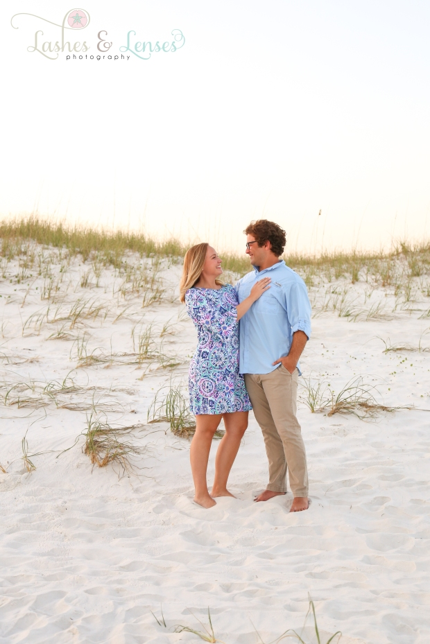 Young couple standing on the sand by a sand dune at Johnson's Beach in Perdido Key