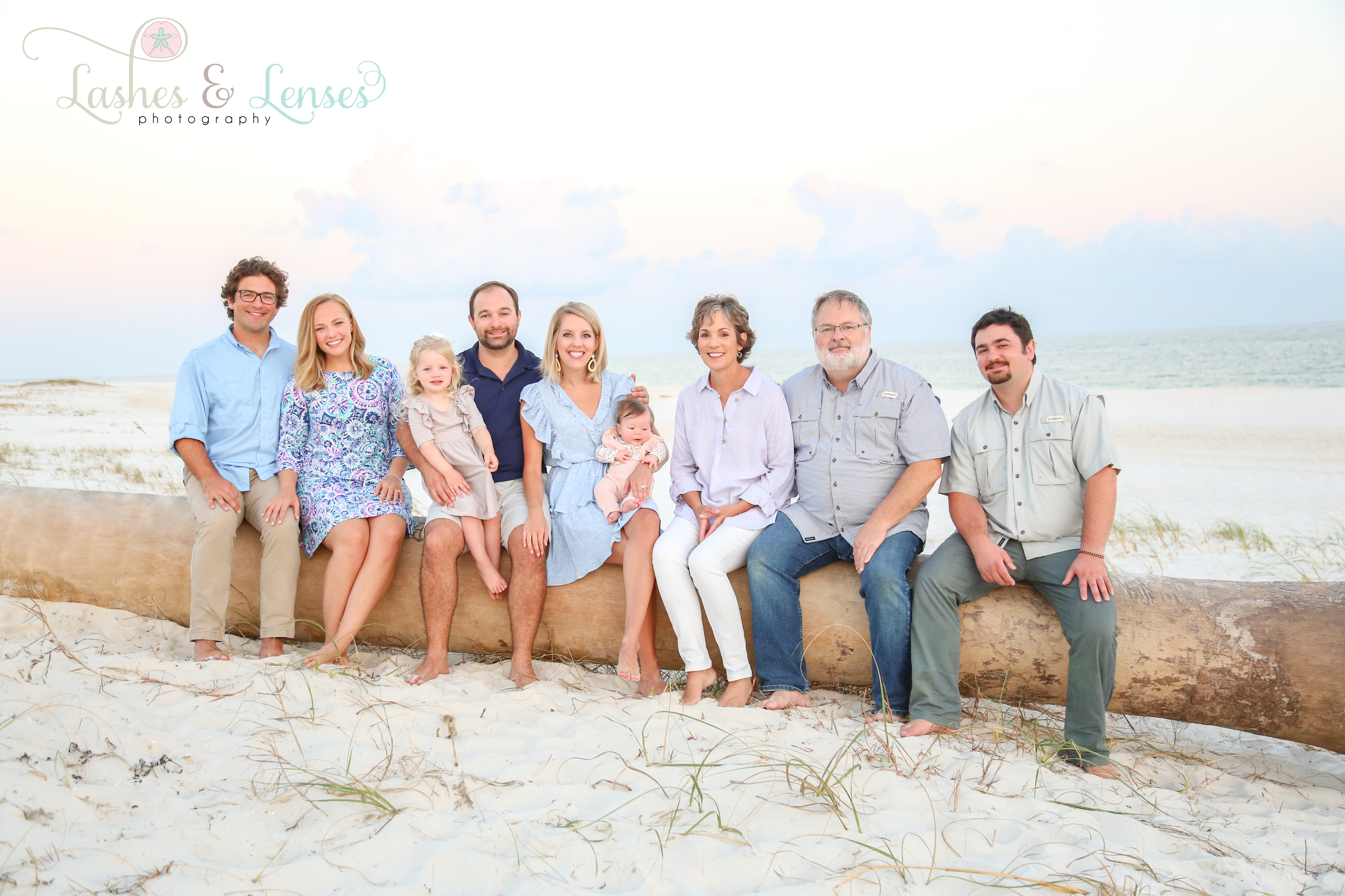 Large family sitting on a large palm tree trunk washed up by a hurricane at Johnson's Beach in Perdido Key