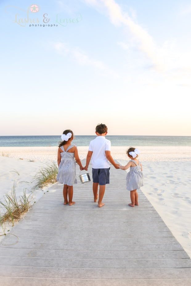 Brother and two sisters on the boardwalk looking at the gulf at Johnson's Beach in Perdido Key