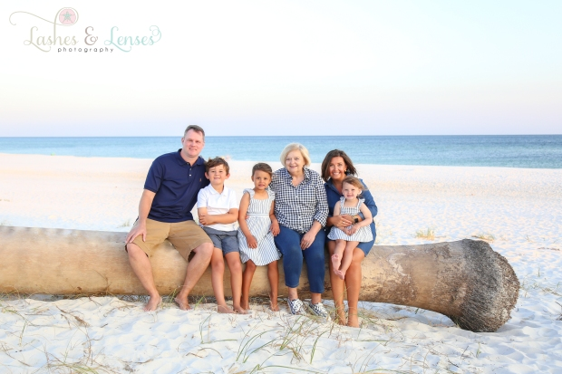 Family with Grandmother sitting on washed up palm tree at Johnson's Beach in Perdido Key