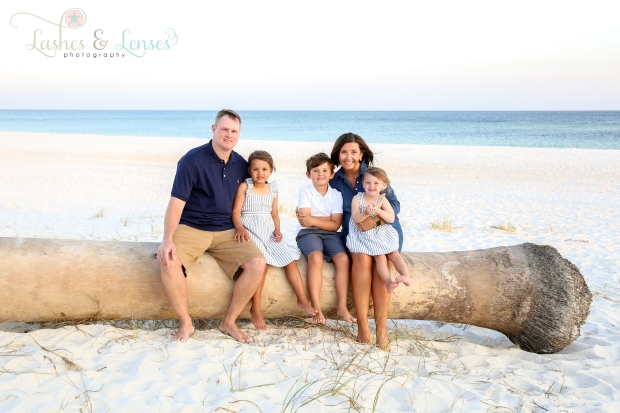Mom and Dad sitting with their children on a washed up log at Johnson's Beach in Perdido Key