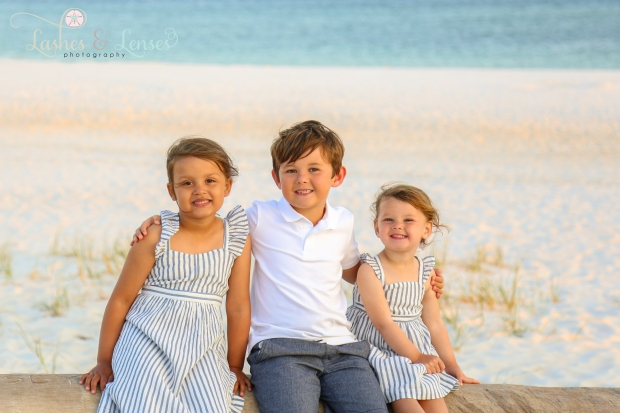 Young siblings sitting on a washed up log on the beach at Johnson's Beach in Perdido Key