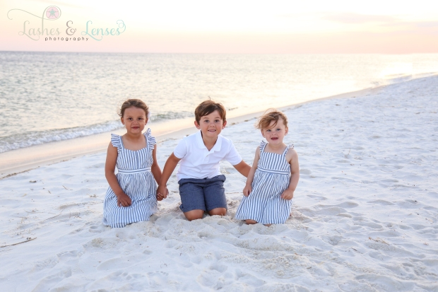 Brother and sisters sitting on the beach at Johnson's Beach in Perdido Key