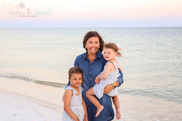 Mom and her daughters standing on the beach next to the water at Johnson's Beach in Perdido Key